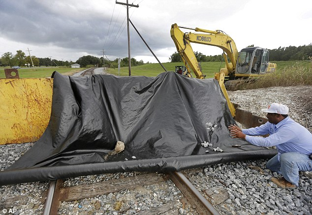 Calm before the storm: Maintenance crews with Plaquemines Parish lift a heavy gate across an opening where train tracks are located in anticipation of Tropical Storm Karen
