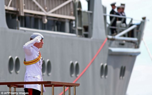 In action: Prince Harry stands and salutes as he arrives at Garden Island in Sydney