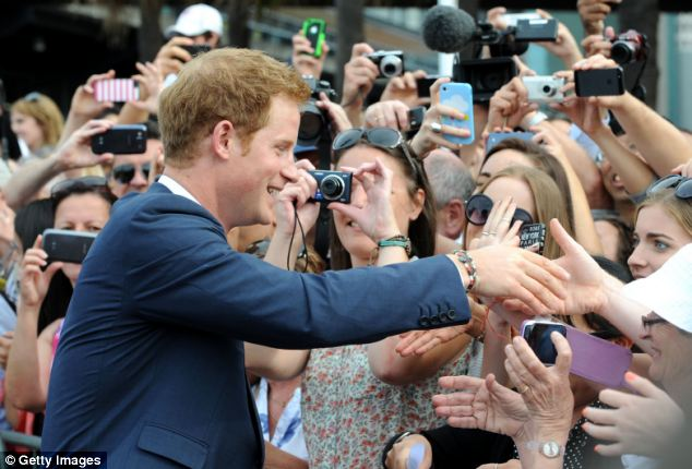 Warm welcome: Harry shakes hands with scores of adoring fans, who take photographs of the Prince with their camera phones