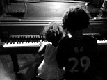 Baby blues: Infant Blue tinkles the ivories with a friend - while Beyonce takes a photograph