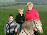 Sharing the burden: Sue Watkinson helps to care for grandsons William, standing, and Freddie, on pony Tarquin