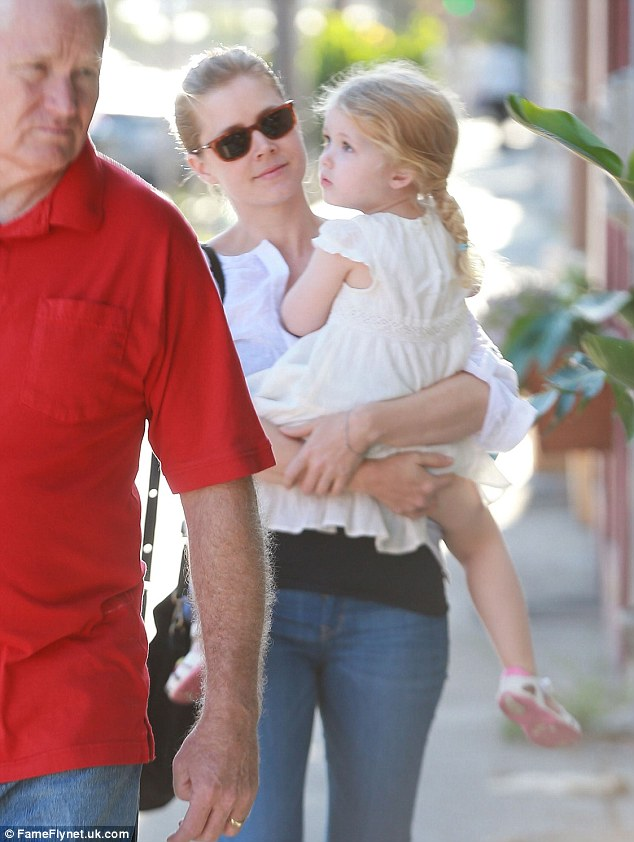 Two of a kind! Amy Adams' gorgeous daughter Aviana hitches a ride with her famous parent after a low-key family outing in Sherman Oaks, California on Saturday