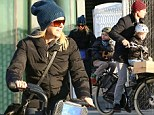 Try to keep up, Mom! Naomi Watts pedals quickly but still lags behind her 'boys' on Citibike spin through New York