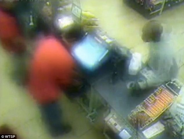 Ready to strike: The man took his hot coffee and threw it at the store clerk that was serving him, and Robert VanConett is seen to the left of his colleague