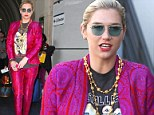 There's no missing her at the baggage claim! Kesha stands out at the airport in a hot pink and purple paisley suit