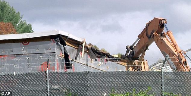 Tearing down: A backhoe rips into the roof of the Sandy Hook Elementary School building in Newtown, Connecticut, as demolition began on Friday