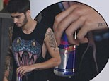 All that touring taking its toll? Zayn Malik looks weary and clutches a Red Bull as he joins One Direction bandmates for yet another concert