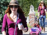 Pushy parent! Alyson Hannigan propels adorable daughter Keeva along in her pink car-shaped trolley during coffee run