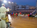 Refusing to budge: The little boy clung on to the Pope's leg as he gave an address to the assembled crowds