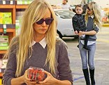Demure on top: Kimberly Stewart wore a plain grey sweater with the white collar of her blouse protuding on Tuesday while grocery shopping with her daughter in Beverly Hils, California