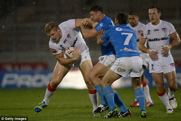 Down: George Burgess of England is tackled by Mark Minichiello during the preparation match at Salford