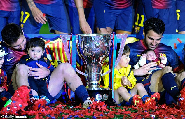 The next generation: Lionel Messi and Fabregas hold their sons as they sit next to the La Liga trophy