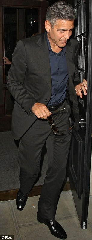 Suited up: George looked dapper in a dark suit and navy blue shirt as he left the restaurant