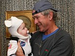 Former First Daughter Jenna Bush tweeted an adorable picture of her baby girl dressed in a NASA spacesuit in the arms of her dad Former President George W. Bush.