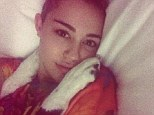 Puppy love? Miley Cyrus tweets shy photo of herself snuggling with her dog after she was caught kissing Benji Madden