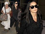 Demi Moore returns to LA with her guru after 'soul searching' pilgrimage to India... as her divorce from Ashton Kutcher nears finalisation