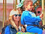 Having a Disney moment: Heidi watches over little Lou as her daughter enjoys a ride on the carousel