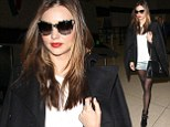 Miranda Kerr shows off her enviably long legs in sheer tights and a tiny denim miniskirt