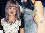 Ouch tat's got to hurt! Kelly Osbourne films the start of her painful process to remove her extensive collection of tattoos