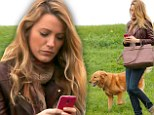 What about your pup? Blake Lively is engrossed in her phone as dog Baxter waits patiently beside her during park stroll