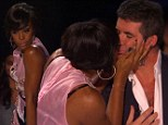 Overcome with emotion: Kelly Rowland planted a kiss on fellow judge Simon Cowell on Wednesday's episode of The X Factor after he gave her singer a good review
