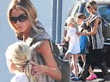 Denise Richards places a protective hand on daughters Sam and Lola after giving up custody of Charlie Sheen's 'violent twins'