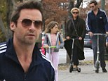 Catch me if you can! Hugh Jackman and wife Deborra trail behind daughter Ava as they take to scooters for the school run