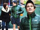Orlando Bloom beams as he strolls arm-in-arm with a mystery woman in New York