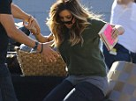 Going, going, gone! Kim Kardashian fails to keep her balance as she falls over while prepping for a yard sale in Ventura