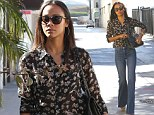 Zoe Saldana looks leggy as she channels the 70s in flared jeans and flowery sheer blouse