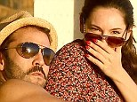 Cover blown: Kelly hides a laugh behind her hand as she is spotted enjoying a romantic sunset date with entourage actor Jeremy Piven