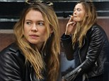Not so glamorous today! Behati Prinsloo relaxes on a concrete bench to puff on a cigarette two days after Victoria's Secret Show