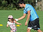 Family matters: Luis Suarez welcomes his daughter Delfina on the training ground as Uruguay prepare for Jordan