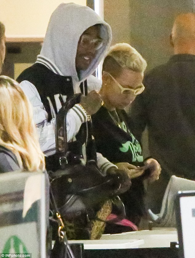 They're famous? Wiz Kalifa and Amber Rose blended in with the crowd as they went through security at Los Angeles International Airport on Friday