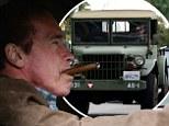 Arnold Schwarzenegger smokes a cigar as he drives a vintage Jeep