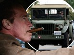 Arnold Schwarzenegger smokes a cigar as he drives a vintage Jeep