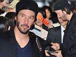Dressed for success! Keanu Reeves looks dapper as he signs autographs in Japan