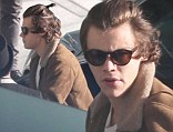 Need a trim? Harry Styles ties his hair up upon as he catches a flight from Heathrow airport