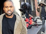 Kanye West's fury at being surrounded by paparazzi during New York stroll, as one snapper is sent flying in scrum