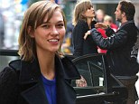 Some help you are! Karlie Kloss meets male friend in New York... but he leaves her to lug her own luggage