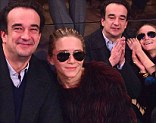 What's his secret? Olivier Sarkozy gets Mary-Kate Olsen smiling as they cuddle up at basketball game