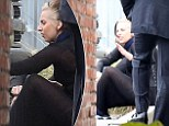 Lady Gaga sits on the ground outside the studio to take a breather, revealing two-tone hair