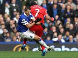 Escaped: Kevin Mirallas of Everton receives a yellow card for this challenge on Luis Suarez