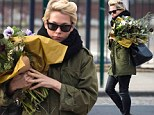 Michelle Williams wrangles the elements and an enormous bouquet of flowers on her windy morning walk
