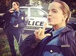 Freeze! Mena Suvari perfects her arrest pose as she is transformed into a police woman