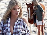 Kate Upton shows off her cleavage as she nuzzles a horse on the beach in Western-themed shoot