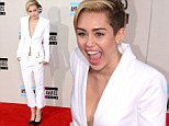 How demure Miley! Cyrus is low key as she arrives in grown-up white suit for the AMAs... but still doesn't wear a bra