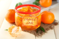 Orange jam with zest and tangerines, on white wooden table