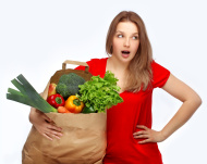 Be vegetarian .Thinking young woman holding vegetable  against w
