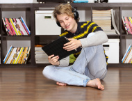 Teenage boy relaxing listening to music  with digital tablet.